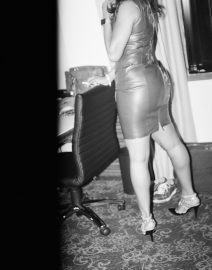 Woman sanding by chair  - overexposed side, Black & White Photo, woman in leather skirt, high heels